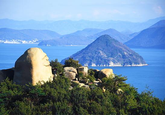 海を眺める巨岩にこにこ岩