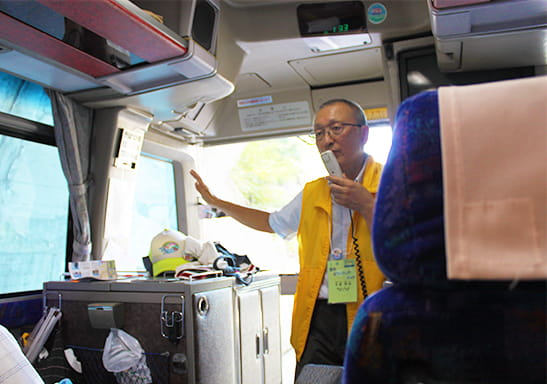 バスの中でマイクを持ってガイドする会長