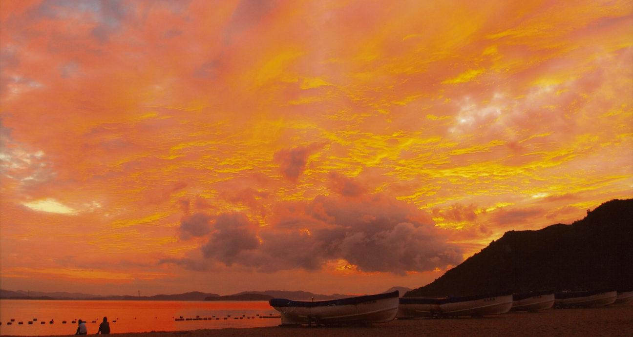 渋川海岸の夕焼けを眺めるカップル