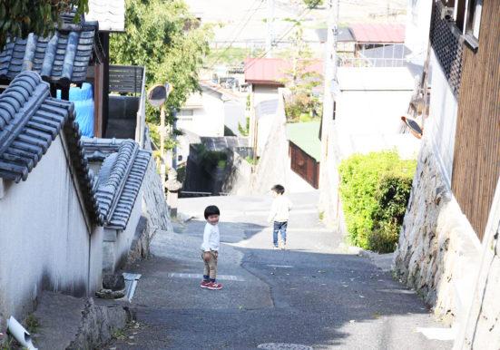 路地の坂道を下る子ども達